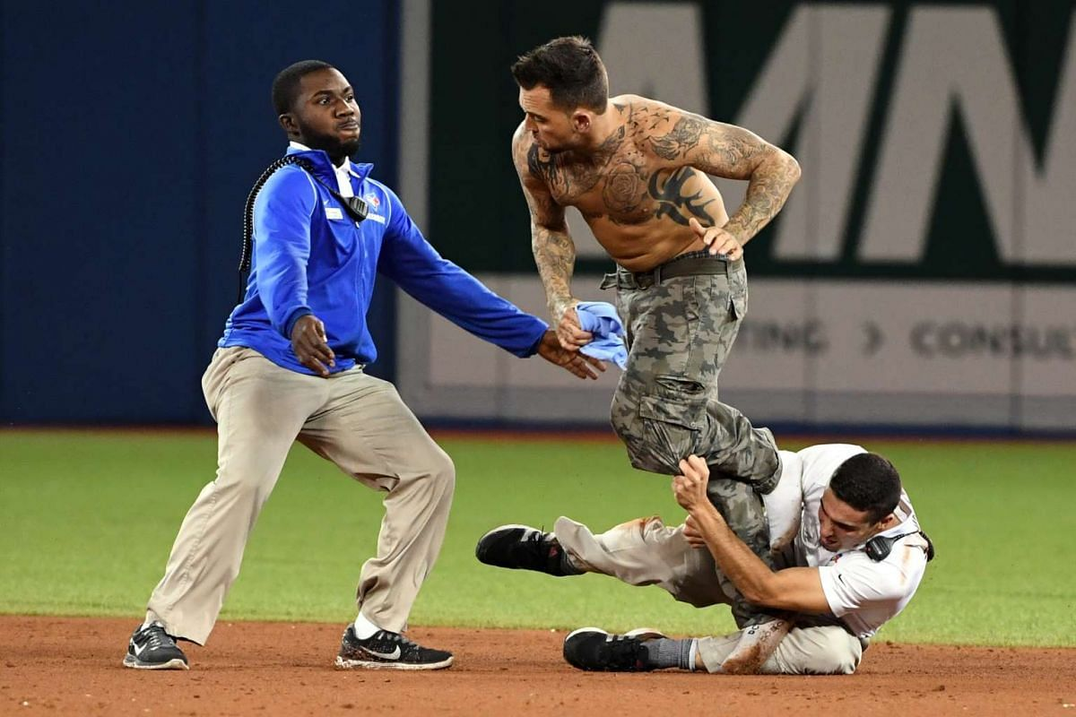 A fan is stopped by security after running onto the field during the ninth inning between the Toronto Blue Jays and the Cleveland Indians in game five of the 2016 ALCS playoff baseball series at Rogers Centre on October 19, 2016: PHOTO: USA TODAY SPO