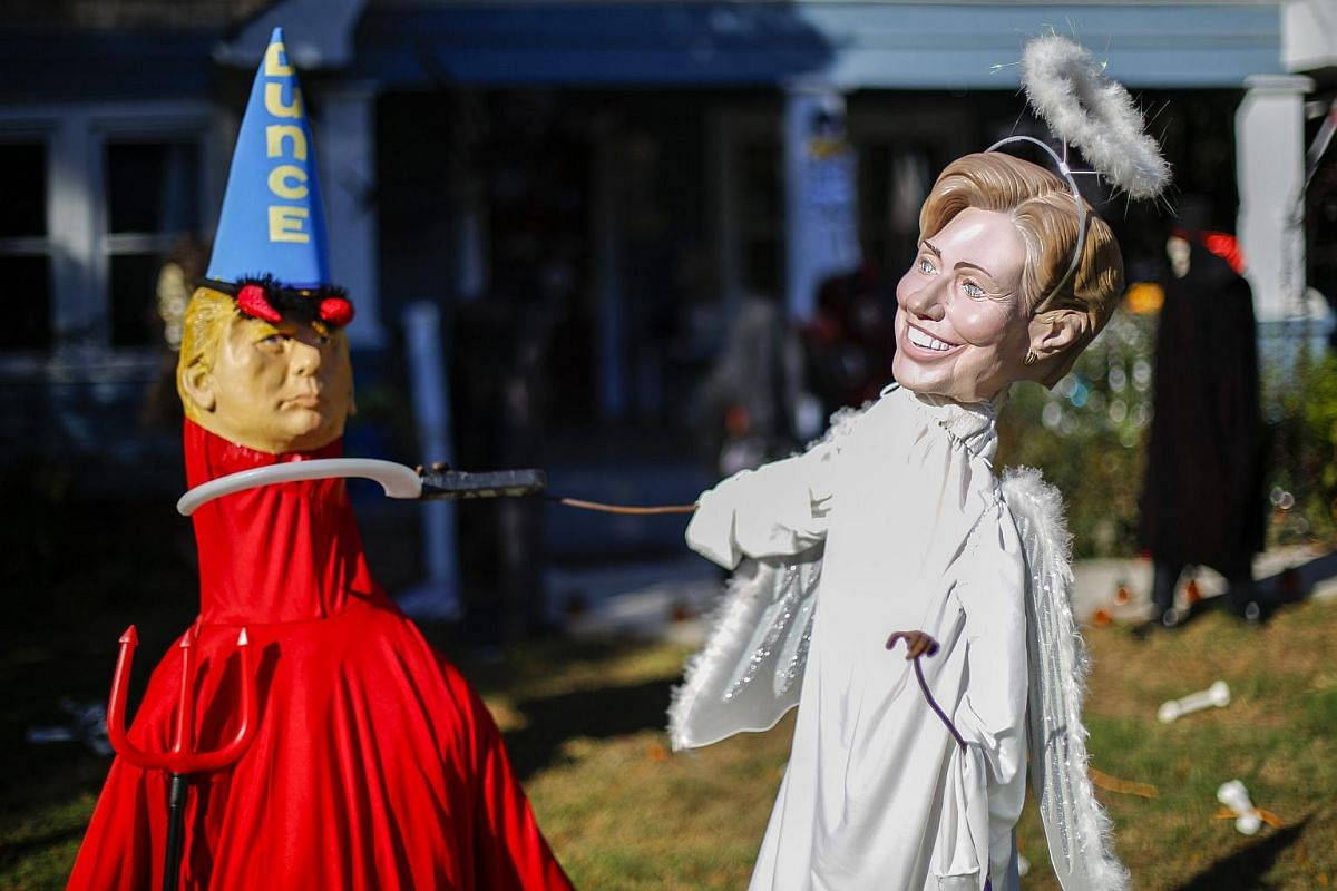 US presidential Democratic nominee Hillary Clinton (right) is depicted as an angel and Republican presidential nominee Donald Trump is depicted as a devil at a home's Halloween display in Georgia on Oct 19, 2016.