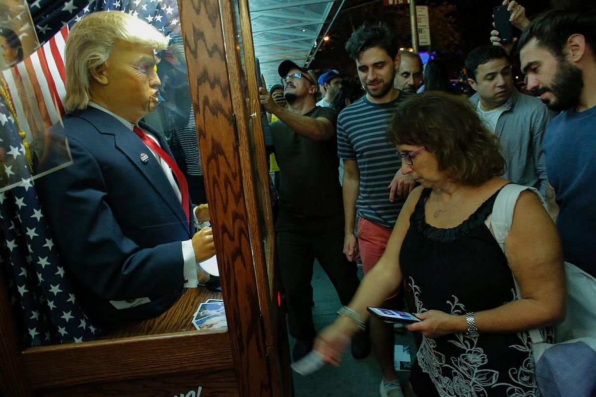 """People view the art installation """"All-Seeing Trump"""", a fortune telling machine created by a group of anonymous Brooklyn-based artists, outside the IFC Theater before the debut of a surprise documentary by US filmmaker Michael Moore about Republican p"""