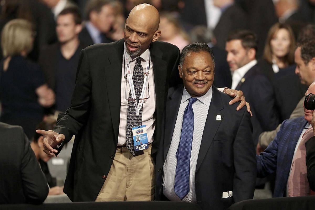 Retired NBA basketball star Kareem Abdul-Jabbar puts his arm around the Reverend Jesse Jackson as they await the start of Mr Donald Trump and Mrs Hillary Clinton's  US presidential debate.