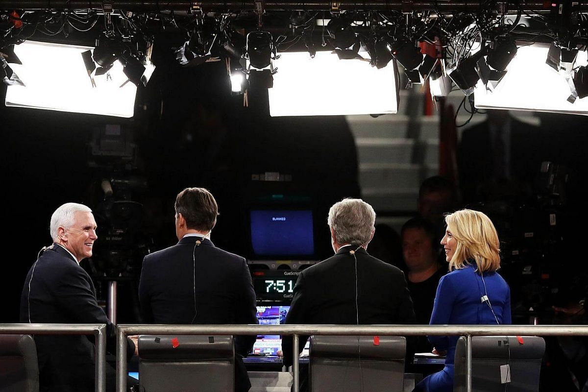 Republican vice-presidential nominee Mike Pence speaks with the CNN broadcast crew before the start of the third US presidential debate.