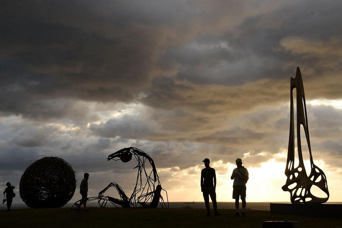 Visitors look at sculptures on display at the annual Sculpture by the Sea exhibition along the Bondi to Tamarama coastal walk in Sydney.