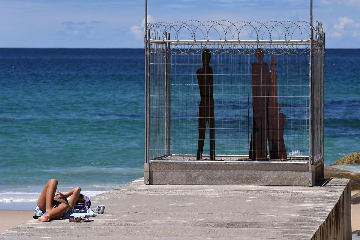 A sun-bather lies next to a sculpture depicting an imprisoned family, part of the Sculpture by the Sea exhibition, in Sydney on Oct 19, 2016.