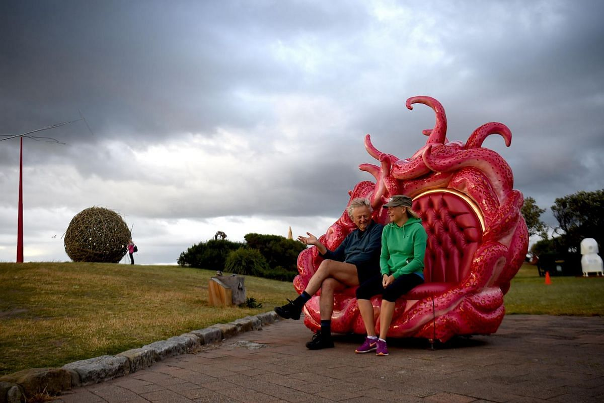 Visitors sit on a sculpture on display at the annual Sculpture by the Sea exhibition in Sydney, on Oct 20, 2016.