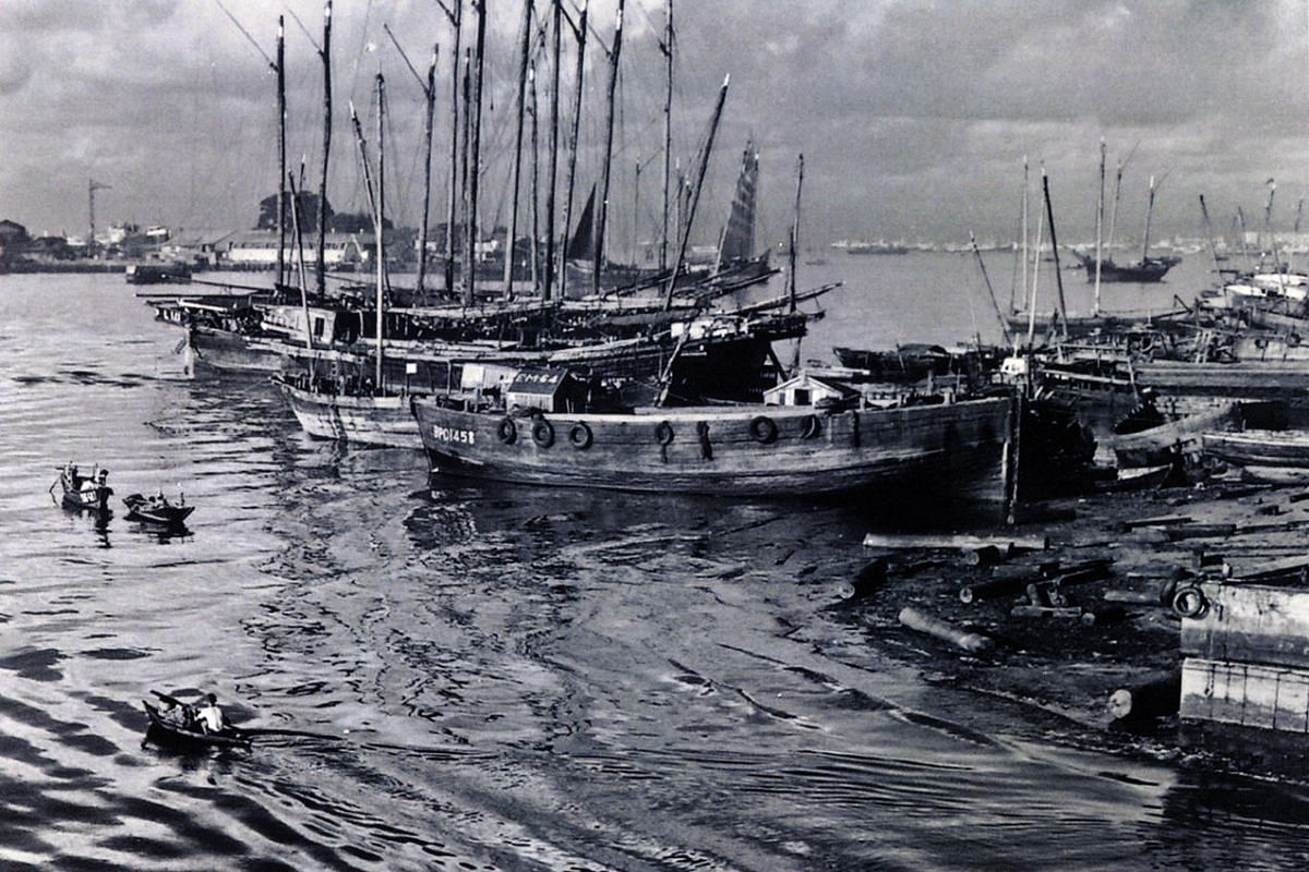 A mixture of fishing, cargo and passenger boats moored off Merdeka Bridge in Singapore in the 1960s or 70s.