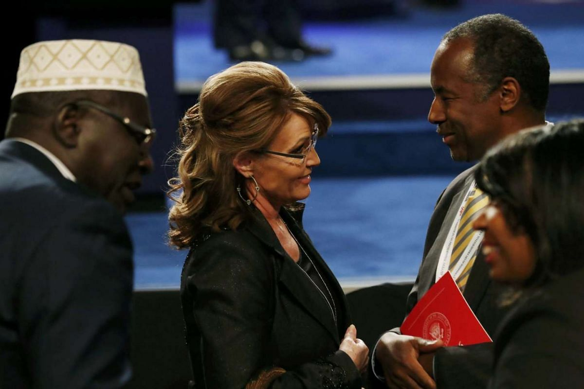 Sarah Palin speaks with Ben Carson near President Barack Obama's half brother Malik (L) after the third and final 2016 presidential campaign debate in Las Vegas, Nevada on October 19, 2016.