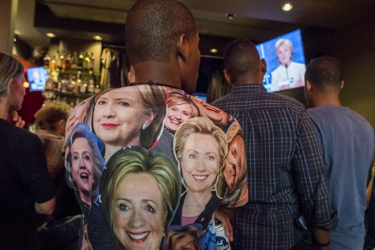 A man wears a shirt with photographs of Hillary Clinton, the 2016 Democratic presidential nominee, while watching the third US presidential debate at a viewing party in San Francisco, California, on Wednesday, Oct. 19, 2016 US time.