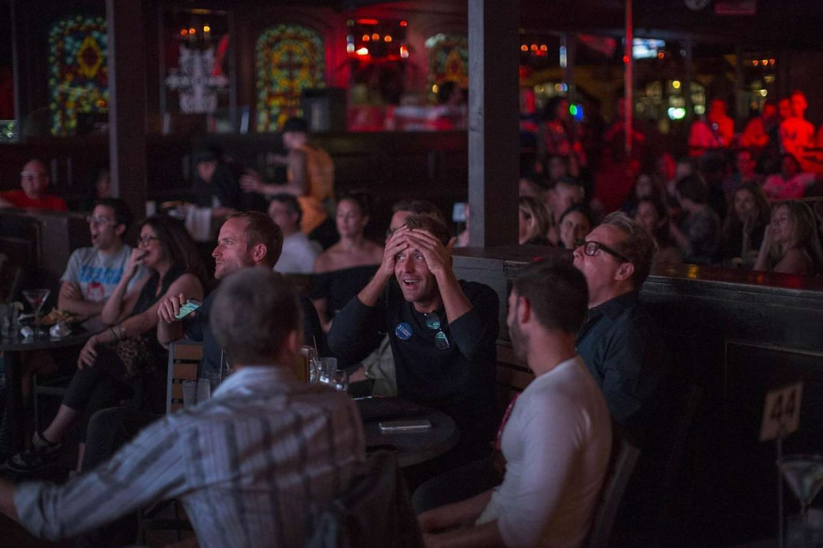 People react at The Abbey bar while watching the third and final presidential debate between Republican Donald Trump and Democrat Hillary Clinton on October 19, 2016, US time, in West Hollywood, California.