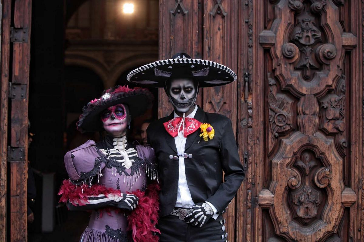 A couple dressed and painted as Mexican popular character Catrina and the Death pose for the media during a press conference presenting the Day of the Dead festivities in Mexico City, Mexico, October 20, 2016. PHOTO: EPA