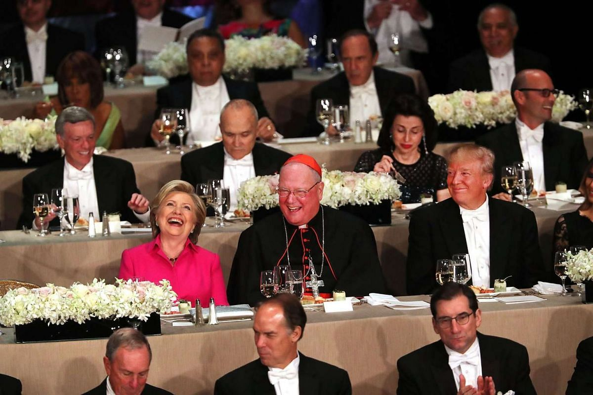 Sitting between Cardinal Timothy Dolan, Hillary Clinton and Donald Trump attend the annual Alfred E. Smith Memorial Foundation Dinner at the Waldorf Astoria on October 20, 2016 in New York City. PHOTO: GETTY IMAGES/AFP