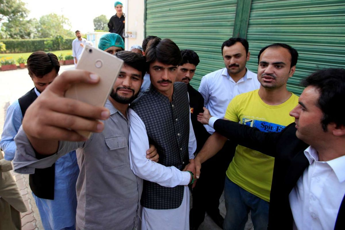 Arshad Khan (C), formerly a chai wala (tea seller) by profession, posses for a selfie with fans after doing a television interview in Islamabad, Pakistan October 20, 2016.  At first the attention interfered in his work, but he has since stopped worki