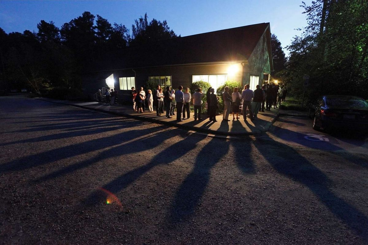 Voters cast shadows as they wait in a line at a polling station open into the evening as early voting for the 2016 general elections begins in Durham, North Carolina, U.S., October 20, 2016. PHOTO: REUTERS