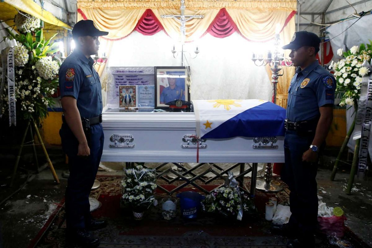 Policemen stand guard in front of the flag-draped coffin of fellow police officer Rancel Cruz, who police investigators said was shot dead by a drug addict, in Manila on Oct 19, 2016.
