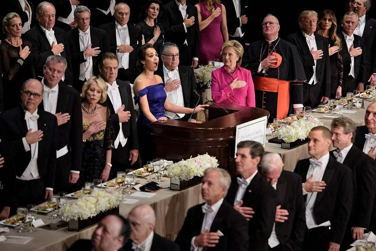 Mrs Hillary Clinton, Cardinal Timothy Dolan, Archbishop of New York, Mr Donald Trump, Mrs Melania Trump and others listen to the National Anthem during the 71st annual Alfred E. Smith Memorial Foundation Dinner at the Waldorf Astoria hotel in New Yor