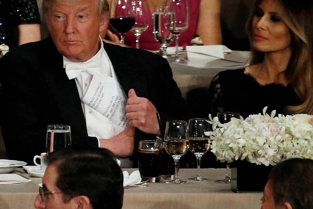 Republican US presidential nominee Donald Trump puts away his notes after speaking at the Alfred E. Smith Memorial Foundation dinner in New York on Oct 20, 2016.