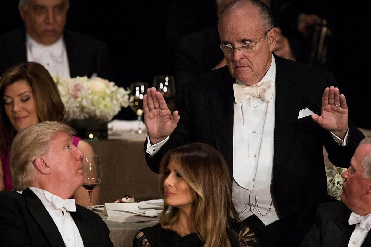 Mr Rudy Giuliani offers advice to Mr Donald Trump at the Alfred E. Smith Memorial Foundation dinner at the Waldorf Astoria hotel in New York on Oct 20, 2016.