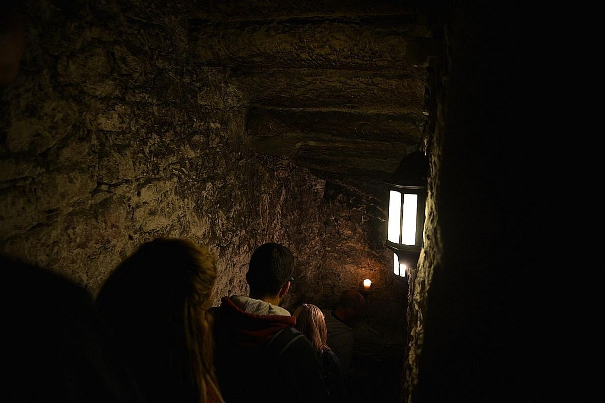 A tour guide taking on the persona of a maid from a blighted era, inside the Gallery Room of The Real Mary King's Close attraction in Edinburgh.