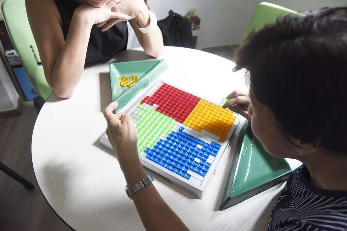 Madam Tan performing a cognitive activity at The Care Library facilitated by a centre employee.