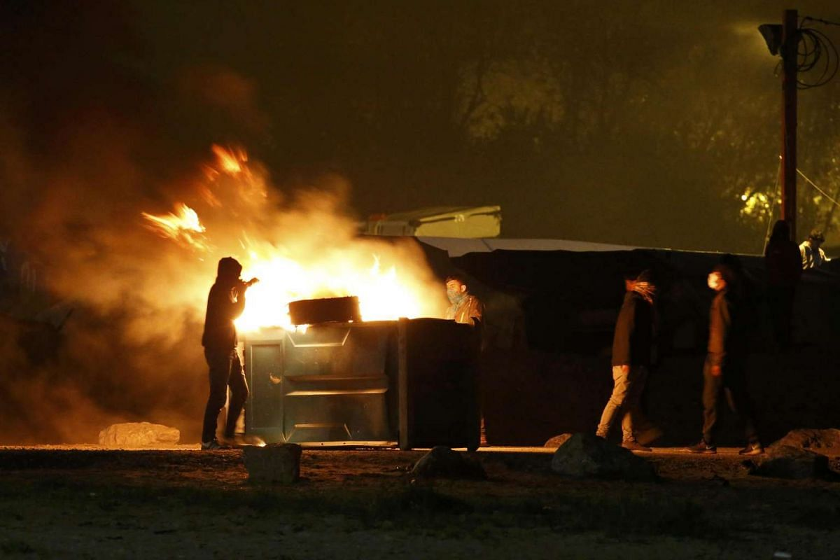 A migrant sets fire to a rubbish bin in the Calais migrant camp in France on Oct 24, 2016.