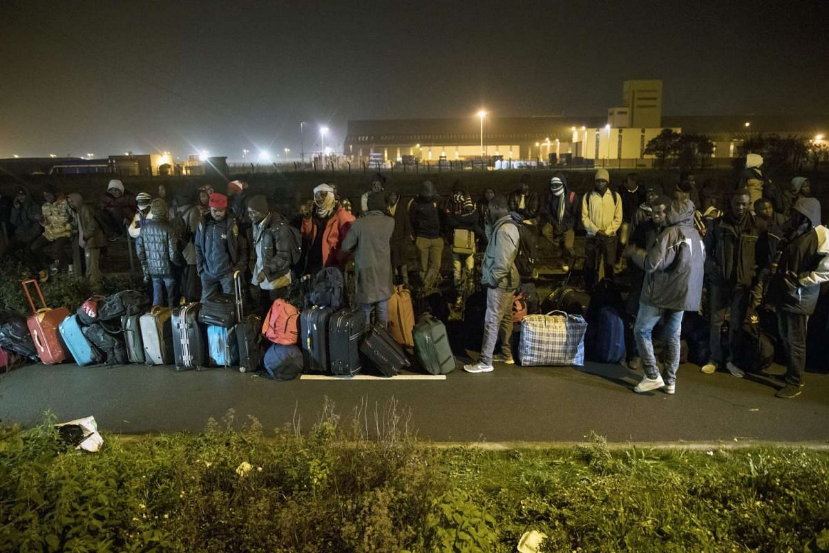 Migrants queue at the start of their evacuation and transfer to reception centers in France on Oct 24, 2016.