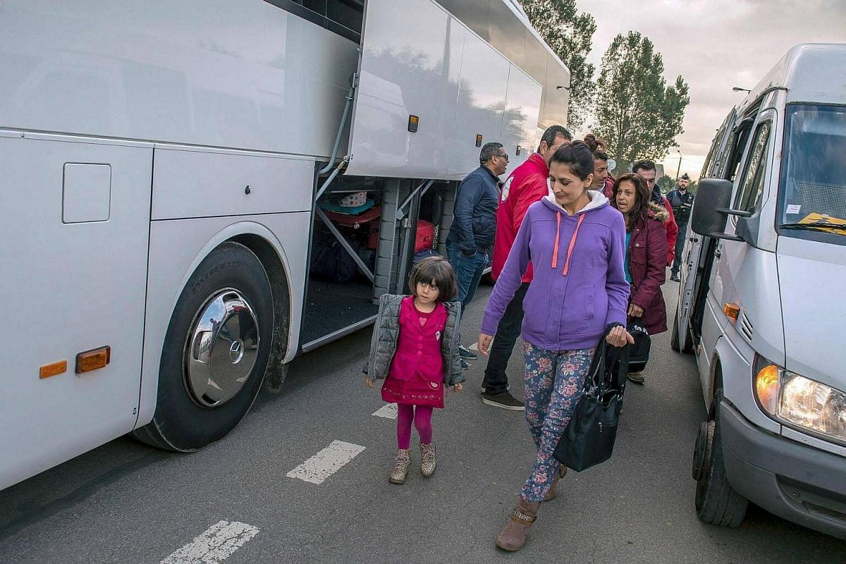 A Kurdish Iraqi family prepares to board a bus to leave the 'Jungle' migrant camp in Calais on Oct 12, 2016.