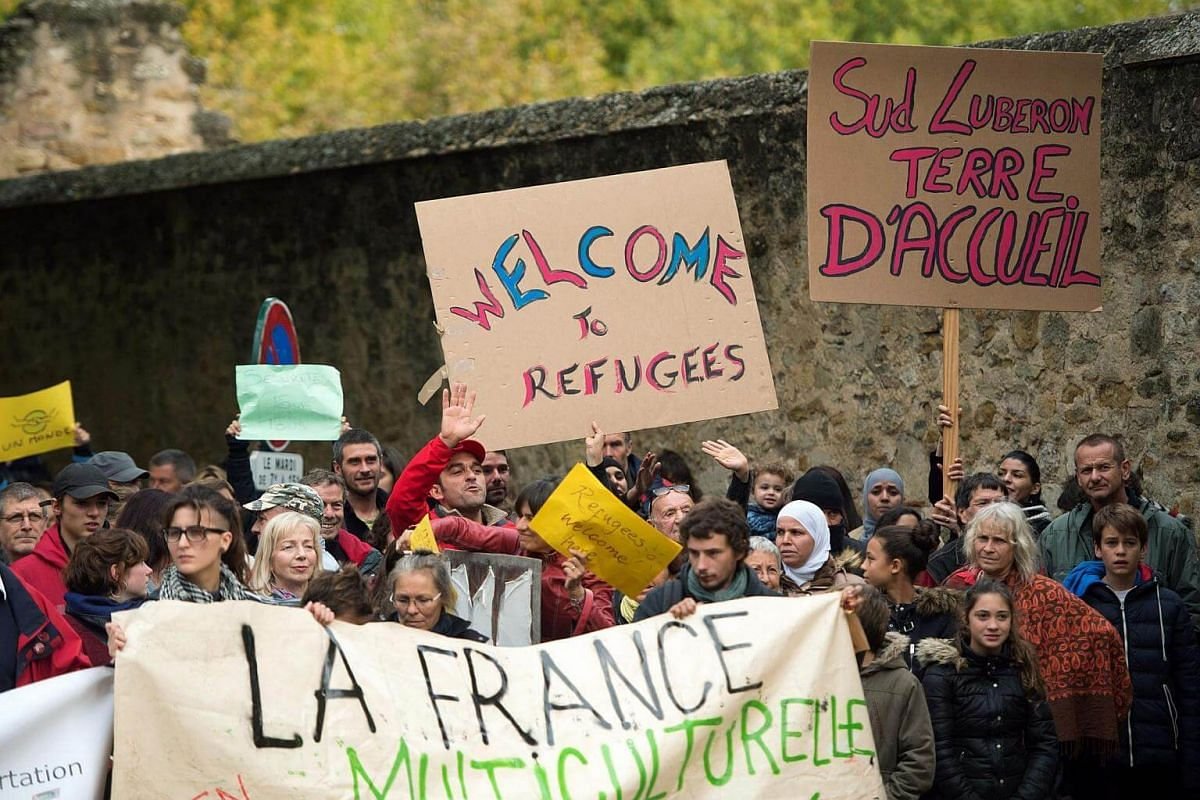 Migrants' sympathizers hold a placard reading 'South Luberon, land of asylum' as they attend a rally in favour of migrants' hosting, on Oct 23, 2016, in La Tour d'Aigues.