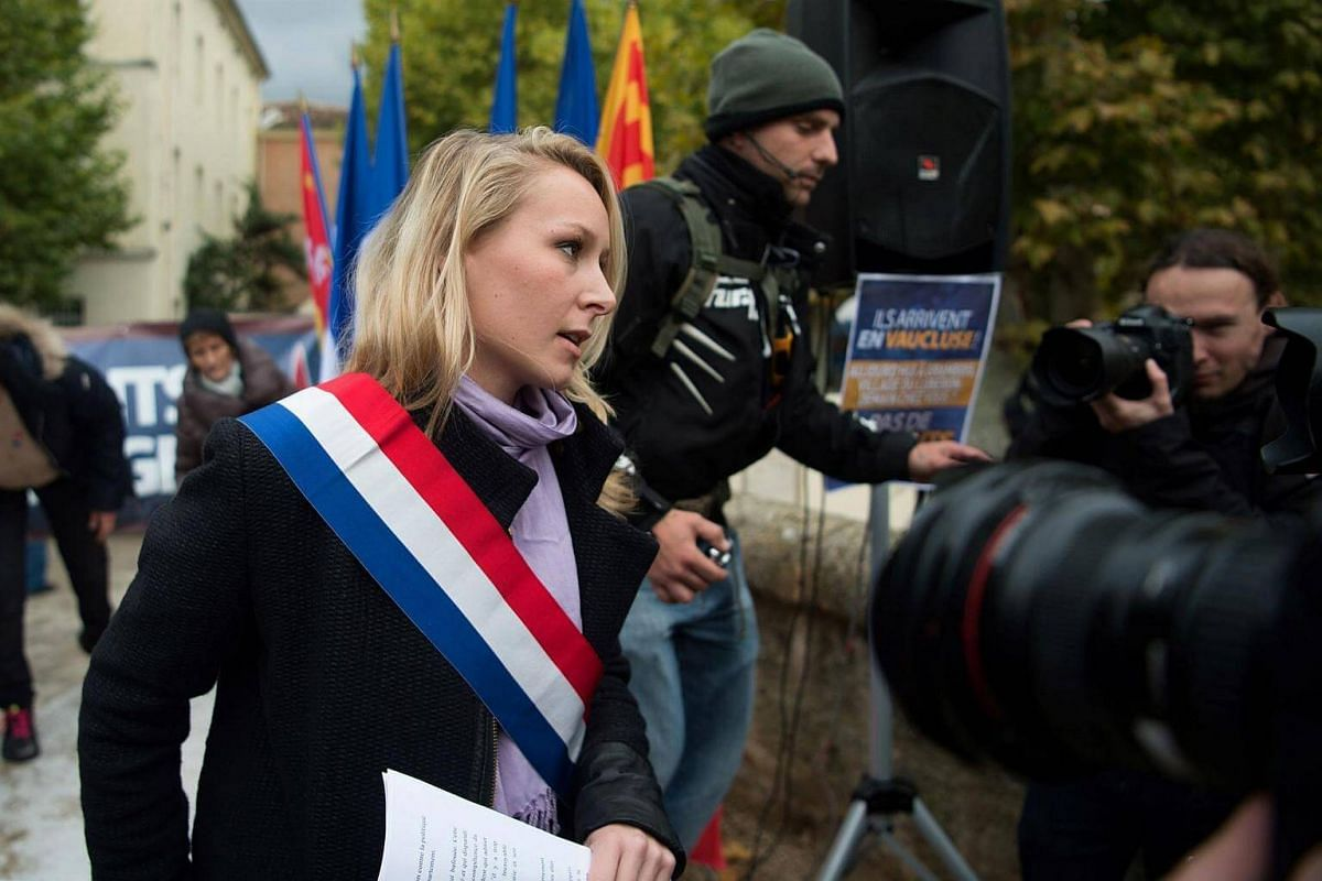 French far-right Front National party's member of parliament Marion Marechal-Le Pen (left) arrives to attend a rally against the hosting of migrants in La Tour d'Aigues on Oct 23, 2016.