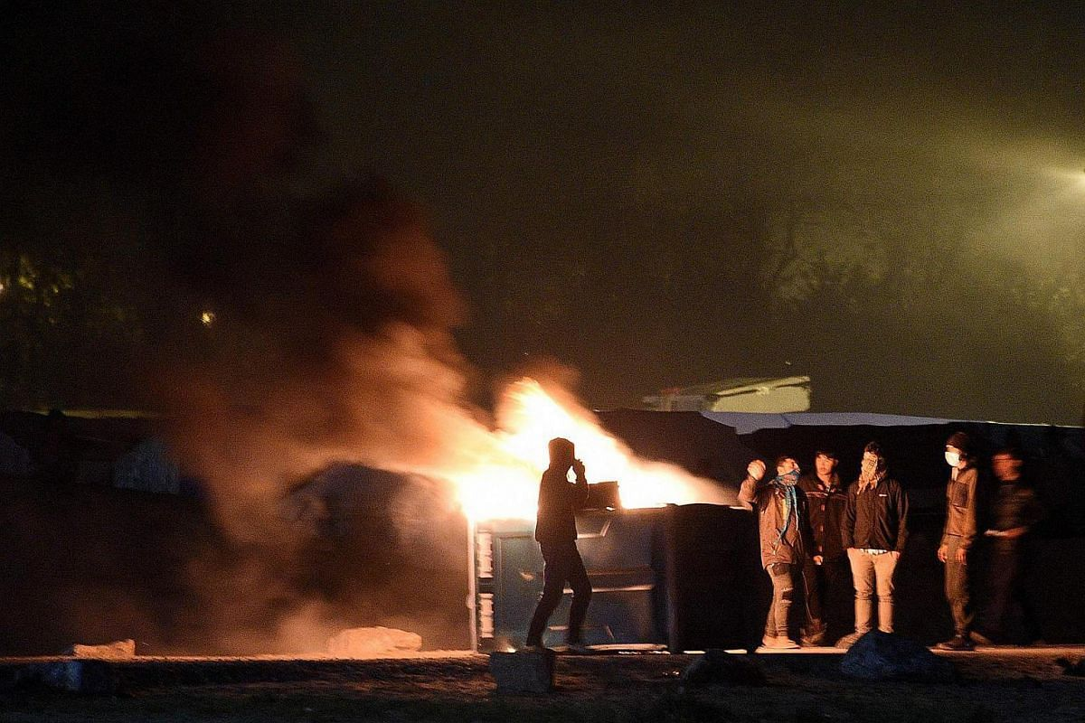 Migrants start a fire during clashes with French police at the 'Jungle' migrant camp in Calais, northern France, on Oct 23, 2016.