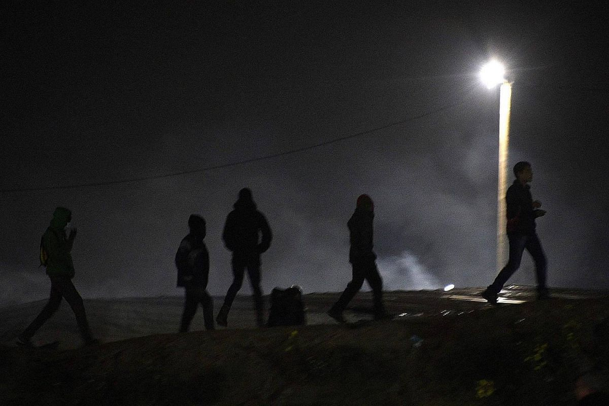 Migrants take cover from tear gas during clashes with French police at the 'Jungle' migrant camp in Calais, northern France, on Oct 23, 2016.