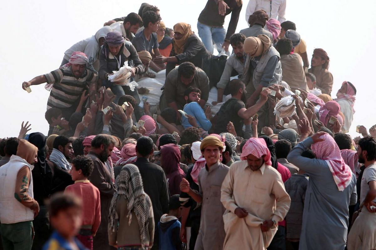 Iraqi refugees that fled violence in Mosul and internally displaced Syrians who fled ISIS-controlled areas in Deir al-Zor, buy food and water near the Iraqi border, in Hasaka Governorate on Oct 23, 2016.