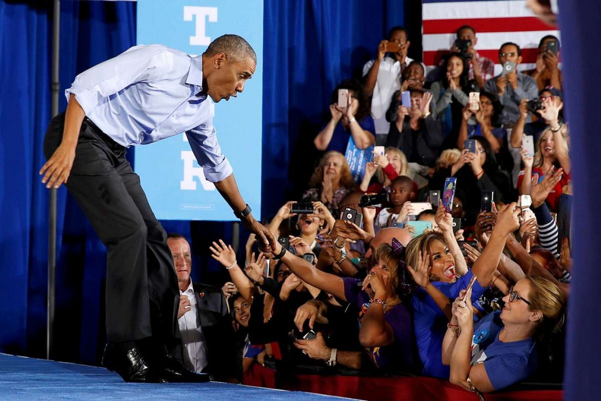 US President Barack Obama reacts as he is almost pulled off the catwalk by a supporter as he arrives to speak at a rally for Hillary Clinton in Las Vegas, Nevada on Oct 23, 2016.