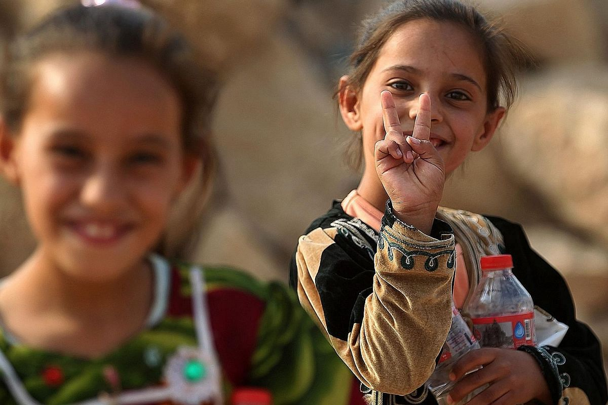 Displaced children from Mosul, whose families fled ISIS militants, at play in Deepaka camp, north-west of Irbil, last Thursday. Above: Iraqi children from the village of al-Khuwayn, south of Mosul, posing for a photo after Iraqi government forces rec