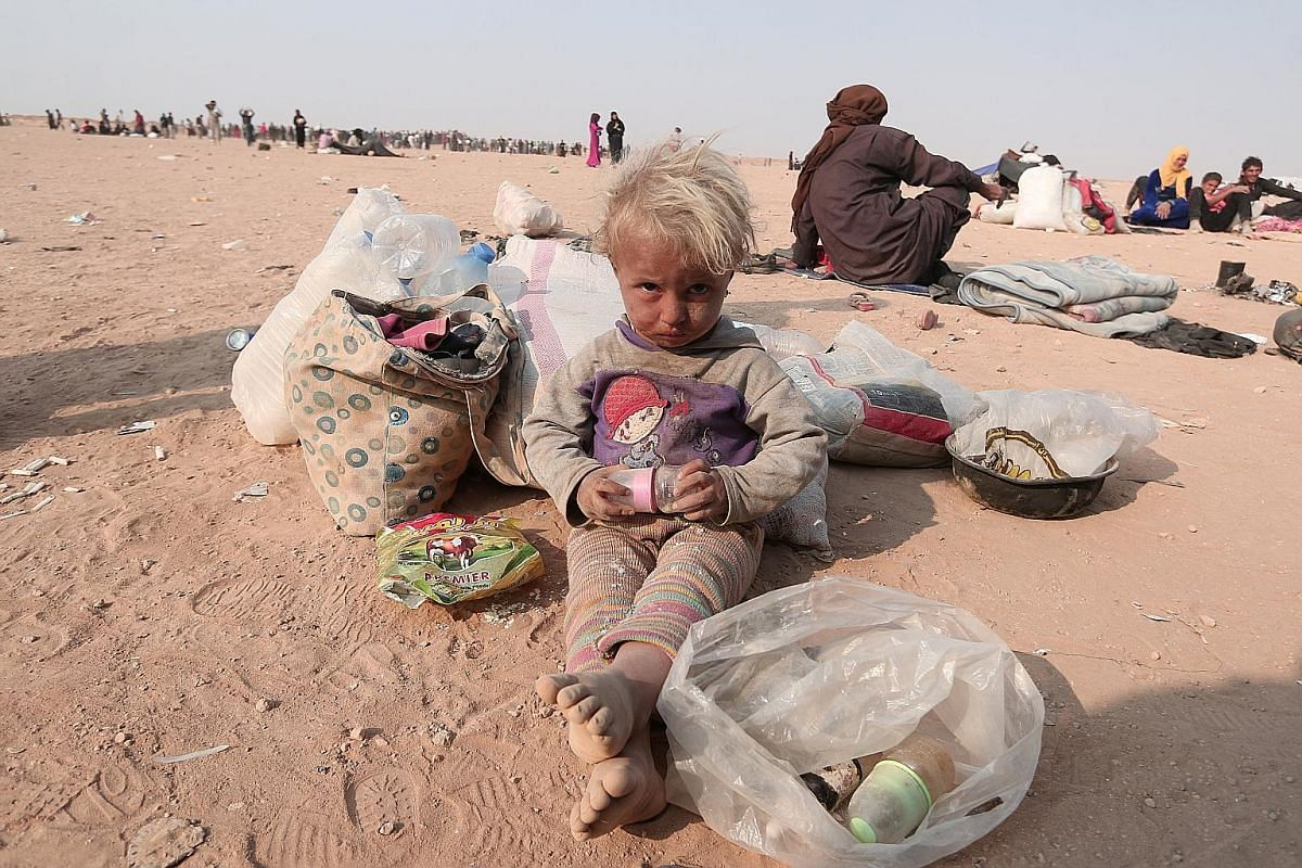 A refugee child among Iraqis who fled violence in Mosul, as well as internally displaced Syrians who fled ISIS-controlled areas in Deir al-Zor, near the Iraqi border in Hasaka Governorate on Sunday.