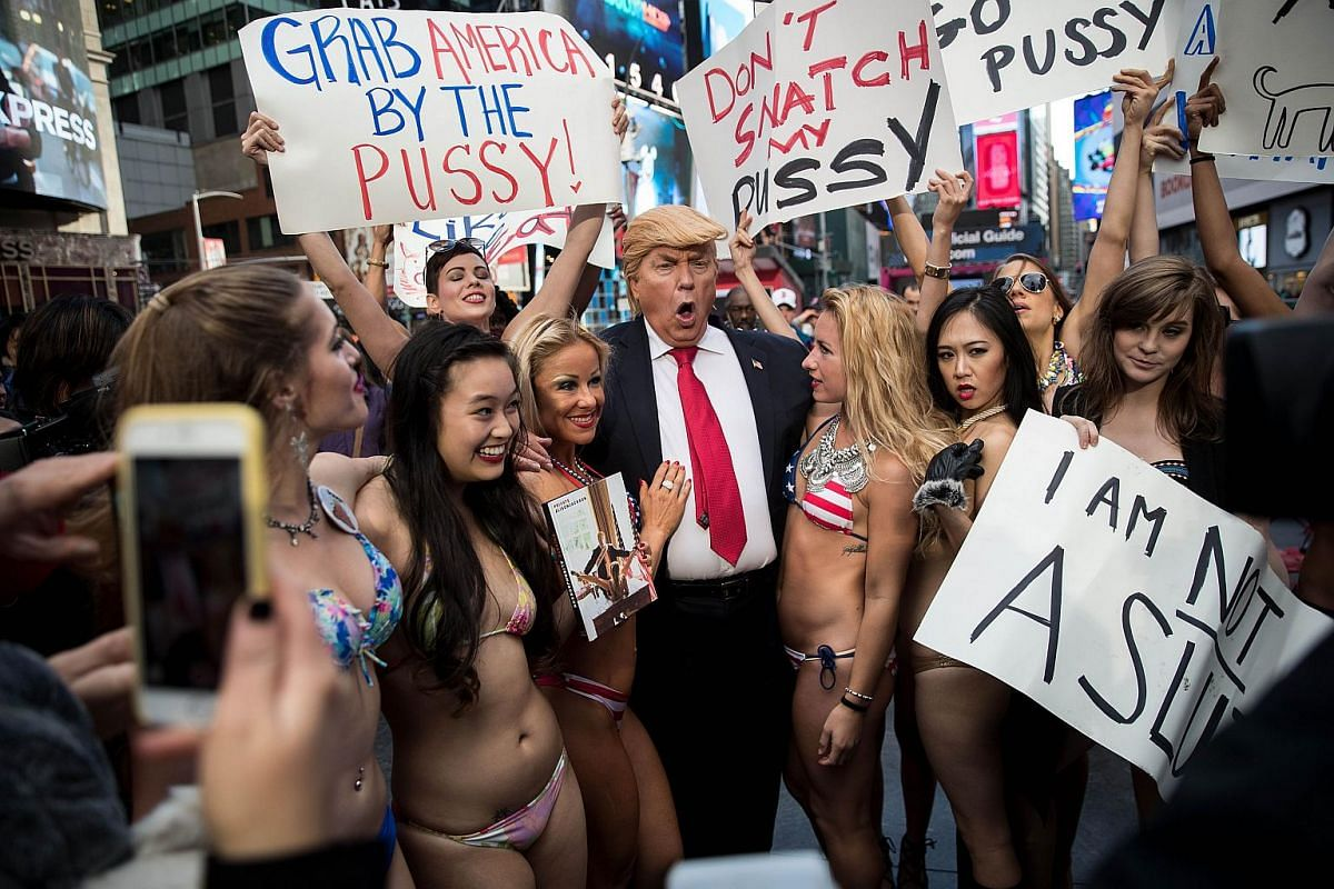 A Donald Trump lookalike poses with bikini-clad women in Times Square, Oct 25, 2016 in New York City.
