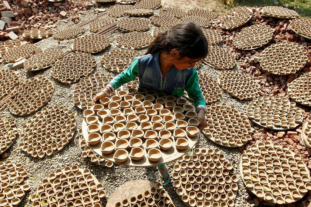 A girl carries dried earthen lamps, which are used to decorate temples and homes during Diwali, the Hindu festival of lights, at a workshop in Chandigarh, India on Oct 23, 2016.
