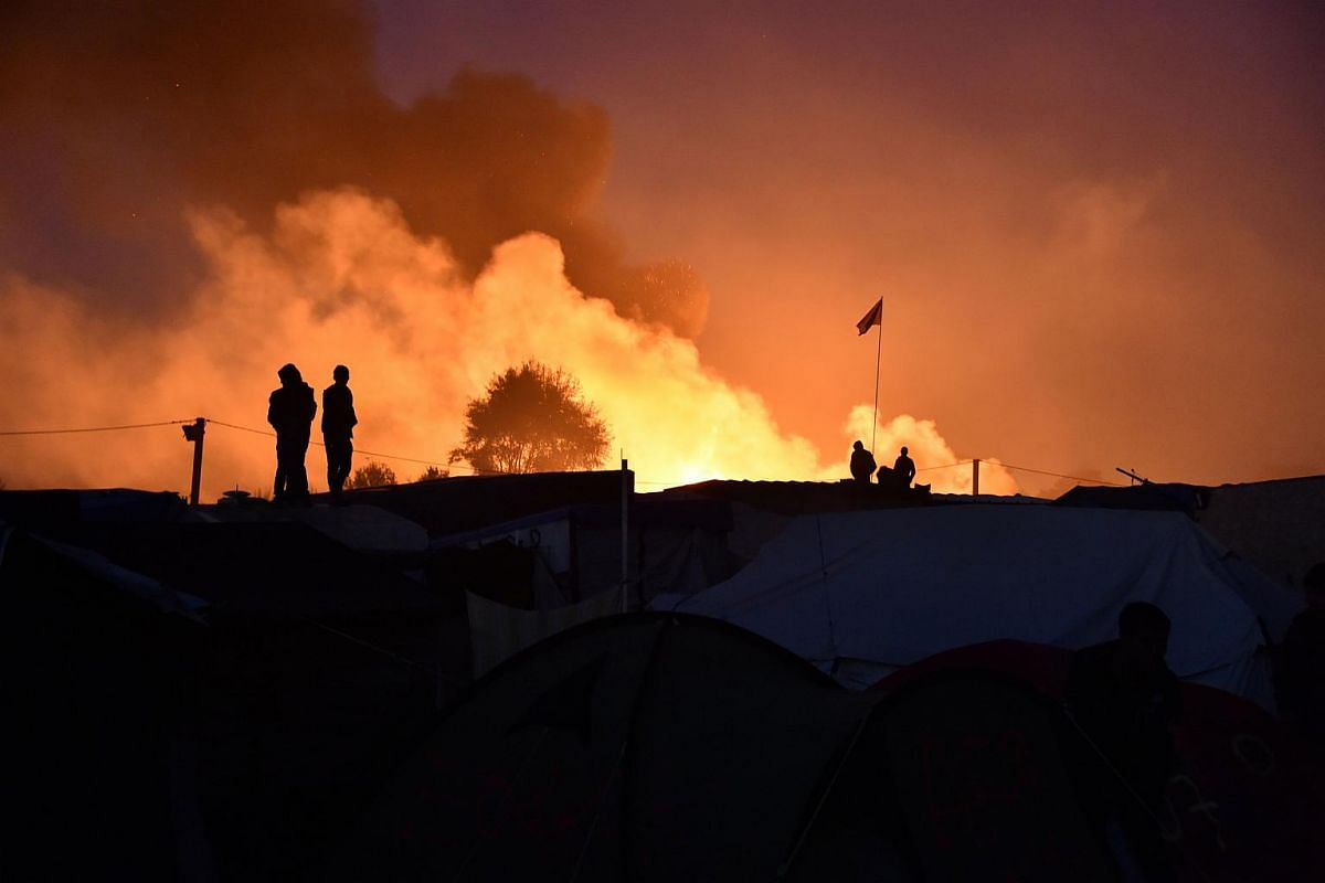 "People look at smoke rising on Oct 25, 2016, during the demolition of the Calais ""Jungle"" camp, in Calais, northern France."