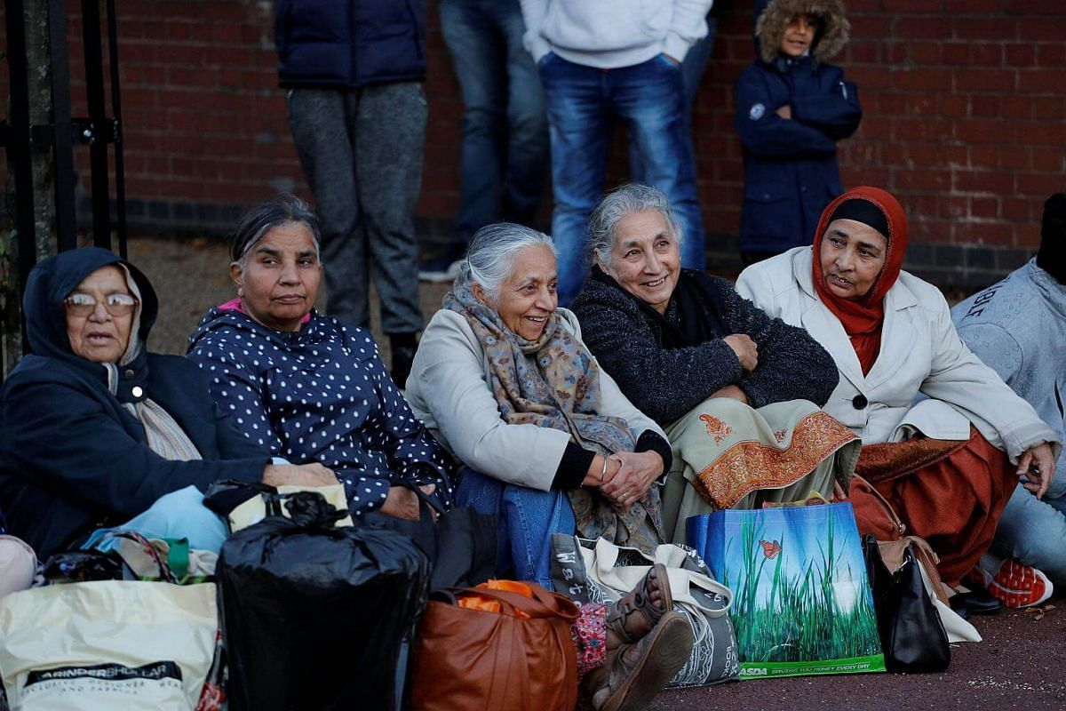 Women wait for the Deepavali lights to be switched on in Leicester, Britain, on Oct 16, 2016.