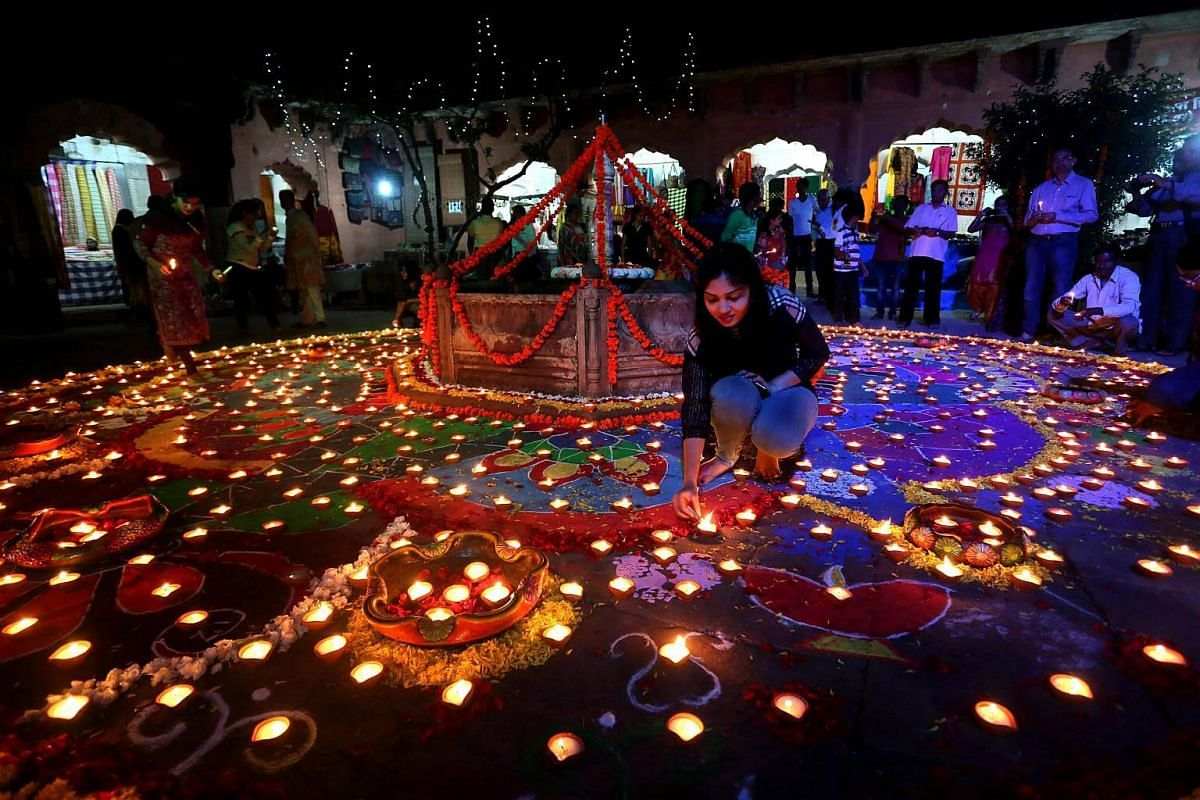 """People light oil lamps during the """"Deep Utsav"""" or Light Festival at the historical Gauhar Mahal palace, as part of the Deepavali festival celebrations in Bhopal, India, on Oct 22, 2016."""