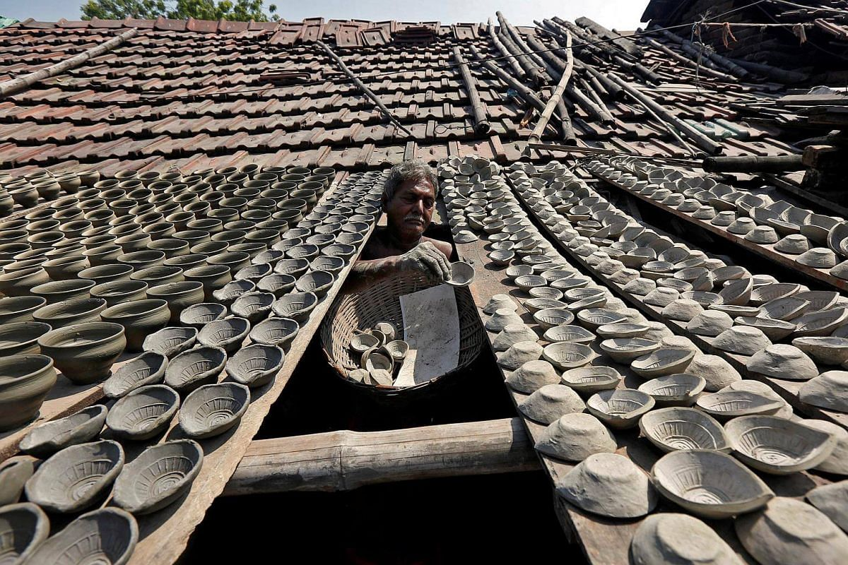 A potter dries earthen lamps, which are used to decorate temples and homes during Deepavali on a wooden slab attached to a rooftop at a workshop in Kolkata, India, on Oct 19, 2016.