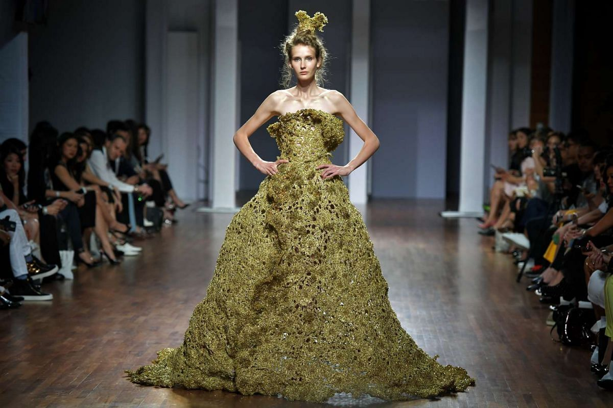 """A model presents a golden gown designed by Guo Pei, who is known for her beaded and embroidered designs in her Spring Summer 2016 """"Courtyard"""" collection, at the National Gallery Singapore on Oct 26, 2016."""
