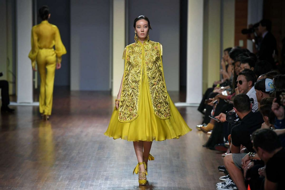 A model walks down the runway in a yellow dress designed by Guo Pei, at the National Gallery Singapore on Oct 26, 2016.