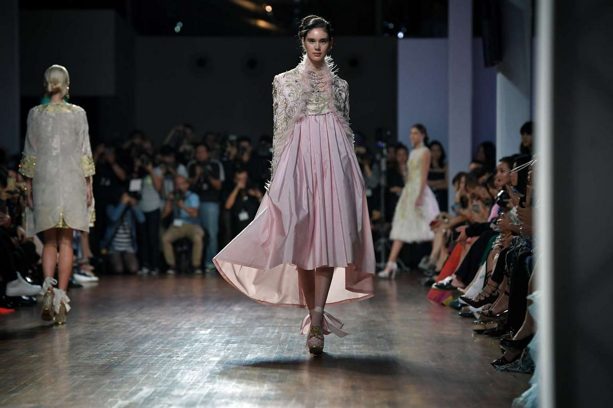 A model walks down the runway in a pastel pink dress designed by Guo Pei as part of her Spring Summer 2016 collection, at the National Gallery Singapore on Oct 26, 2016.
