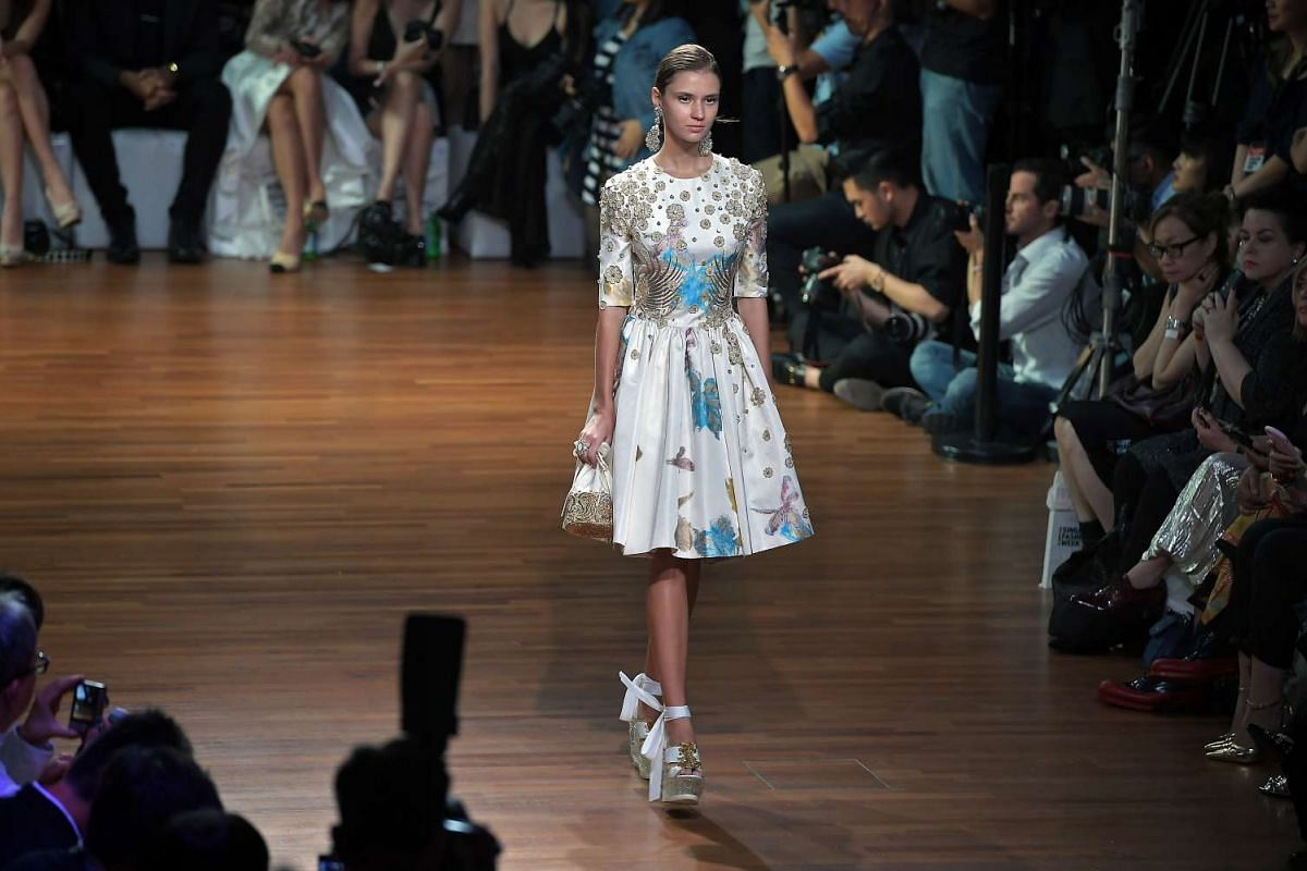 A model presents a dress designed by Guo Pei on the runway at the National Gallery Singapore on Oct 26, 2016.