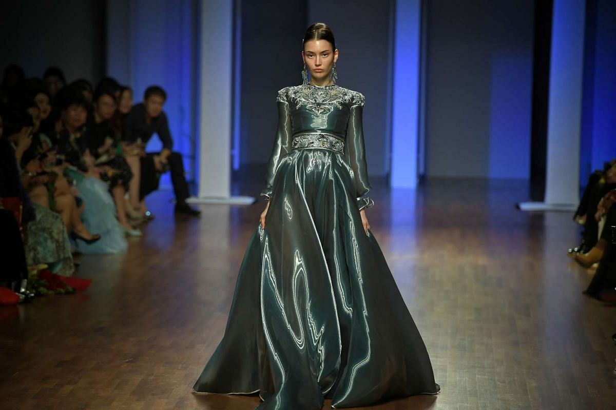 A model presents a green gown designed by Guo Pei on the runway at the National Gallery Singapore on Oct 26, 2016.