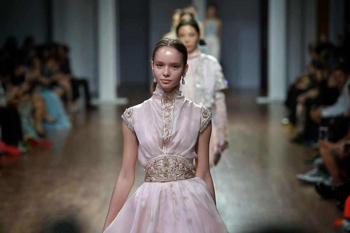 A model walks down the runway in a pale pink dress with embroidery details designed by Guo Pei at the National Gallery Singapore on Oct 26, 2016.