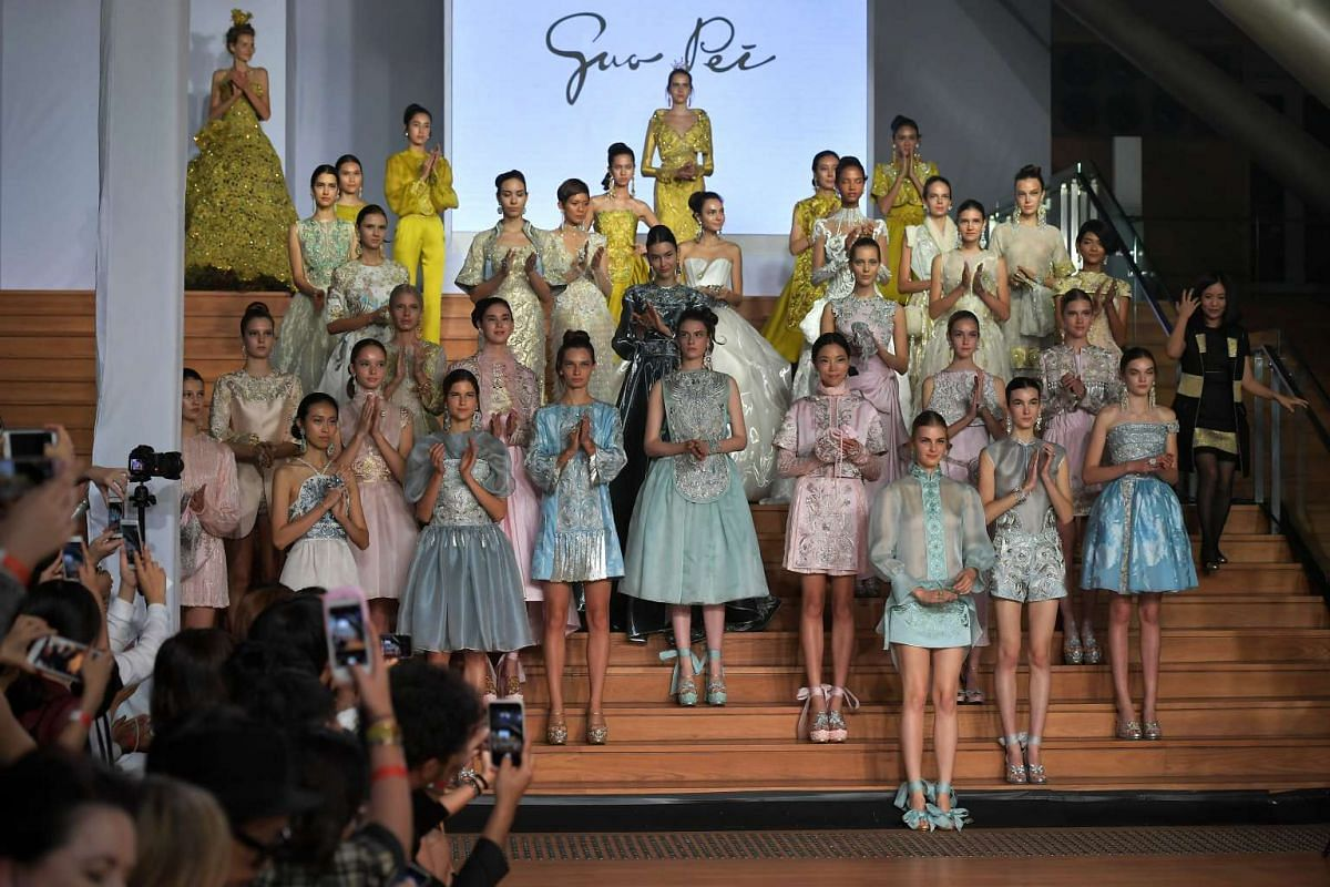 Fashion designer Guo Pei (right) on stage with models wearing her creations at the National Gallery Singapore on Oct 26, 2016.