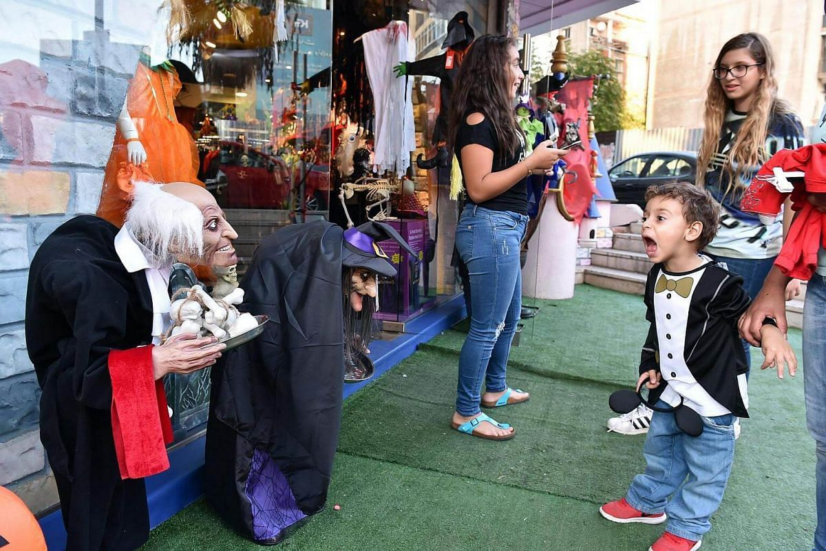 A boy reacts to the Halloween decorations and costumes displayed for sale outside a shop in Beirut, Lebanon, on Oct 26, 2016.