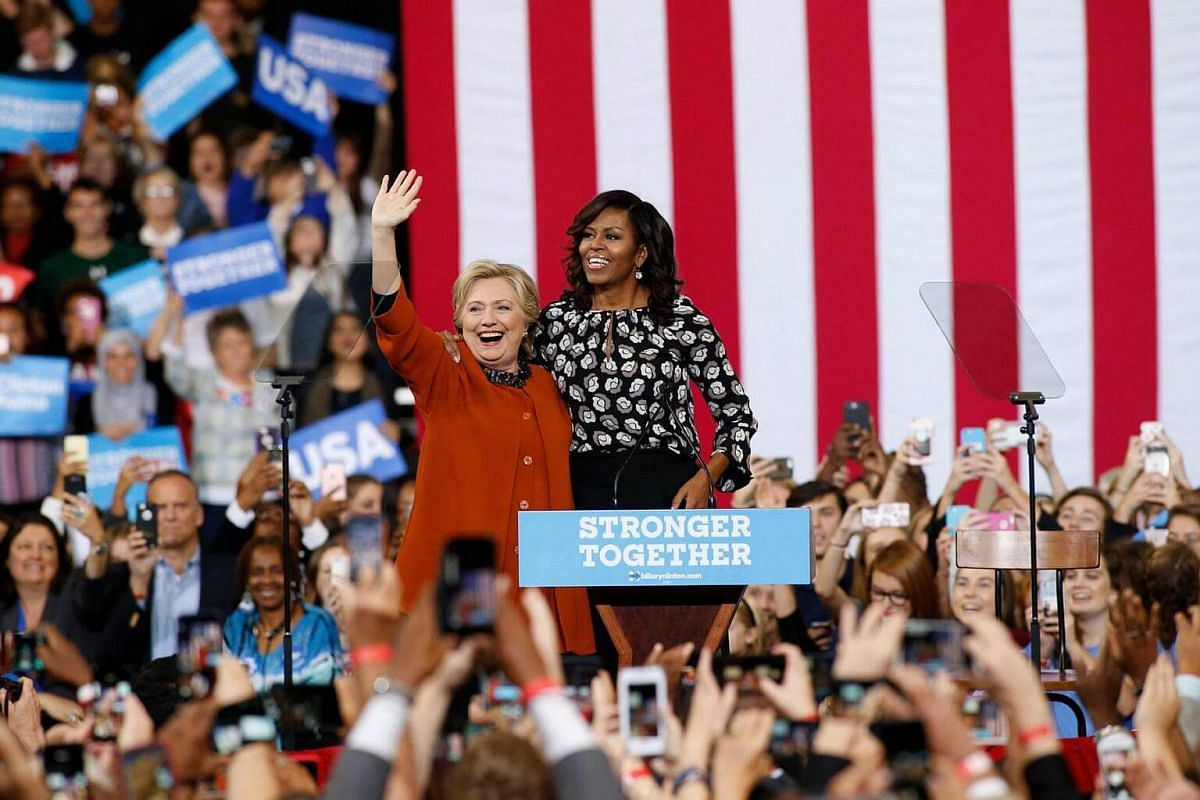 US Democratic presidential candidate Hillary Clinton and US First Lady Michelle Obama arrive to speak to supporters during a presidential campaign event at the Lawrence Joel Veterans Memorial Coliseum in Winston-Salem, North Carolina, US, on Oct 27,
