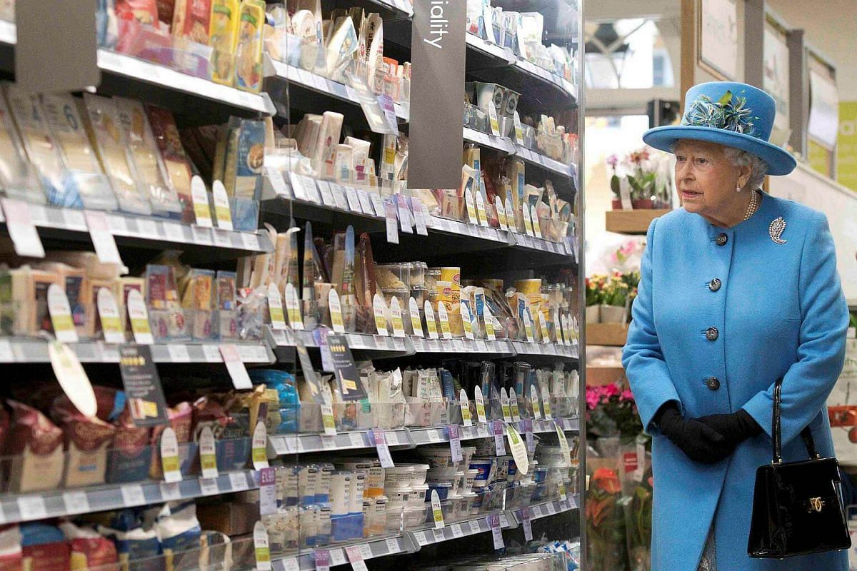Britain's Queen Elizabeth looks at products on the shelves at a Waitrose supermarket during a visit to the town of Poundbury, Britain on Oct 27, 2016.