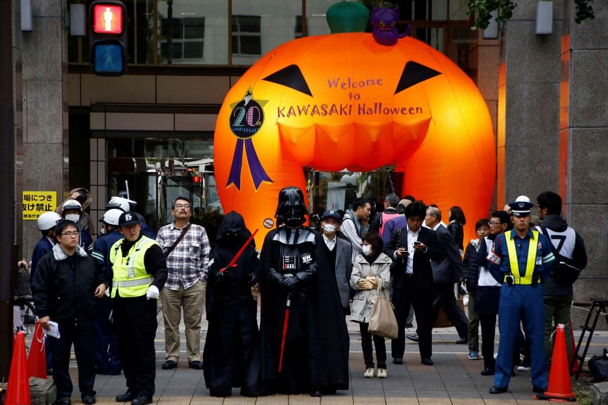 Participants dressed as characters from the Star Wars movies wait for the traffic signal before the Kawasaki Halloween event in Kawasaki city on Oct 30, 2016.